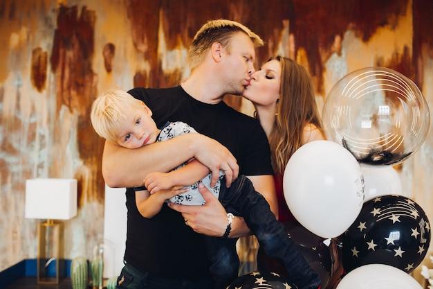 Heureux père et mère s'embrassant tandis que l'homme tenant le fils dans les mains