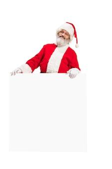 Heureux père noël surpris pointant sur une bannière publicitaire vierge avec espace de copie