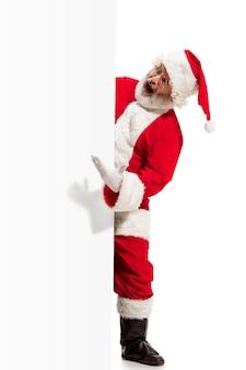 Heureux père noël surpris pointant sur fond de bannière publicitaire vierge avec espace de copie. homme senior souriant montrant à blanc vierge d'affiche vide