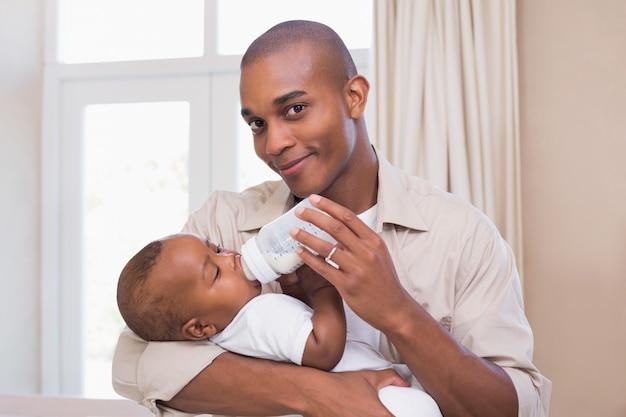 Heureux père nourrir son petit garçon une bouteille