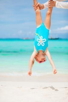 Heureux père et petite fille sur la plage de sable blanc s'amusent ensemble