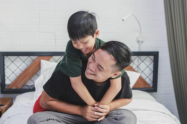 Heureux père portant son fils et souriant ensemble