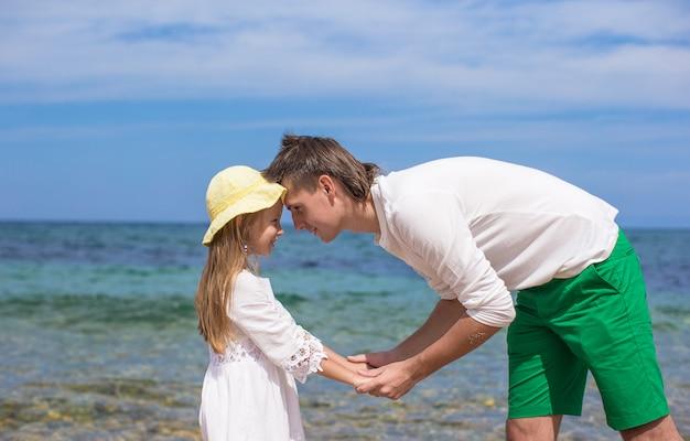 Heureux père et sa petite fille adorable à la plage par une journée ensoleillée