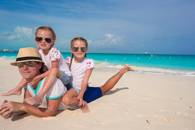 Heureux père et ses adorables petites filles sur une plage tropicale