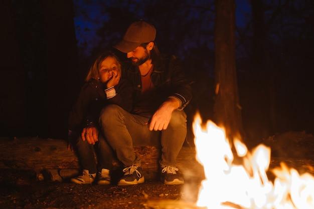 Heureux père et son fils se réchauffent au coin du feu assis dans une étreinte sur des bûches lors d'une randonnée dans la forêt la nuit. .