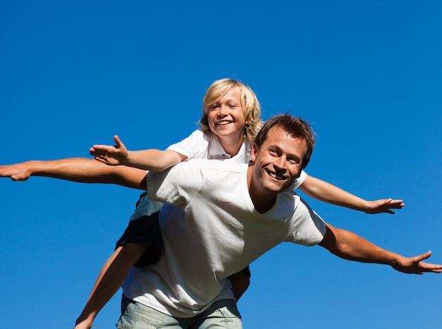 Heureux père avec son fils sur son dos en plein air