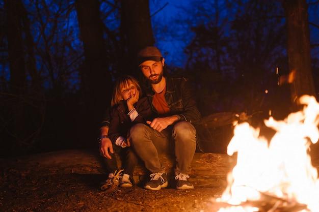 Heureux père et son petit fils assis ensemble sur les bûches devant un feu lors d'une randonnée dans la forêt la nuit. .