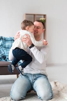 Heureux père tenant un enfant à la maison