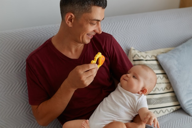 Heureux père tenant un jouet et jouant avec son bébé garçon ou fille assis sur un canapé, homme souriant portant un t-shirt marron montrant à l'enfant un poisson orange, une parentalité heureuse.