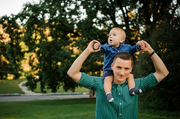 Heureux père tenant un petit garçon vêtu de la chemise à carreaux sur les épaules