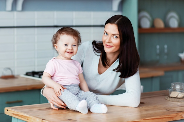 Heureux petit bébé assis sur la table de la cuisine avec maman et souriant