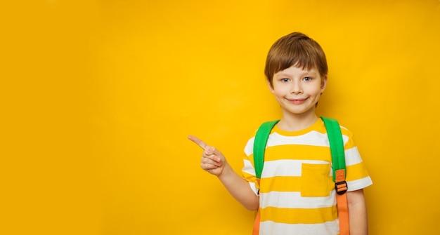 Heureux petit écolier pointant le doigt sur l'espace de copie de fond jaune