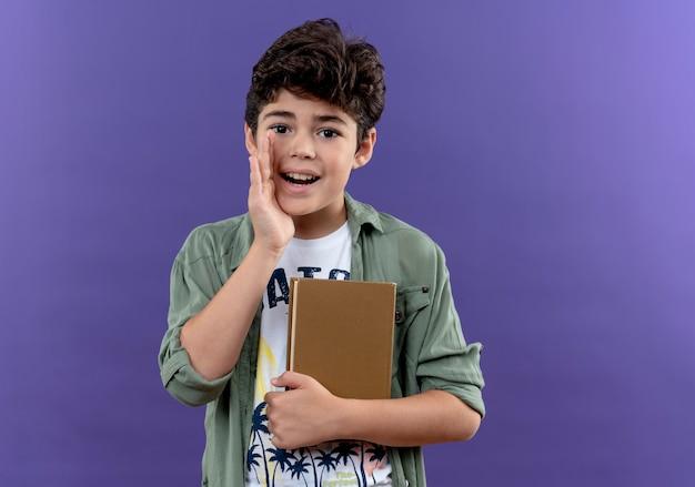 Heureux petit écolier portant sac à dos tenant livre et chuchotement isolé sur mur violet