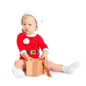 Heureux petit enfant en bonnet de noel avec boîte-cadeau de noël, isolé sur blanc