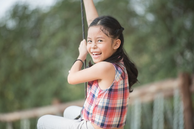 Heureux petit enfant de fille asiatique s'amuser à jouer dans l'aire de jeux en été avec le sourire et rire visage souriant sain et drôle adorable belle fille.