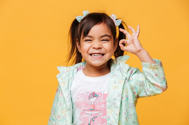 Heureux petit enfant fille montrant un geste correct.