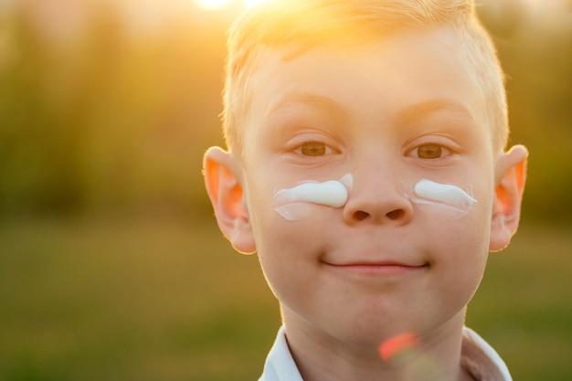 Heureux petit fils appliquant un écran solaire hydratant spf sur le visage dans le parc