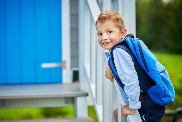 Heureux petit garçon d'âge préscolaire avec sac à dos posant à l'extérieur