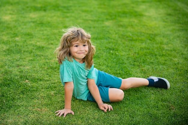 Heureux petit garçon allongé sur l'herbe dans le parc.