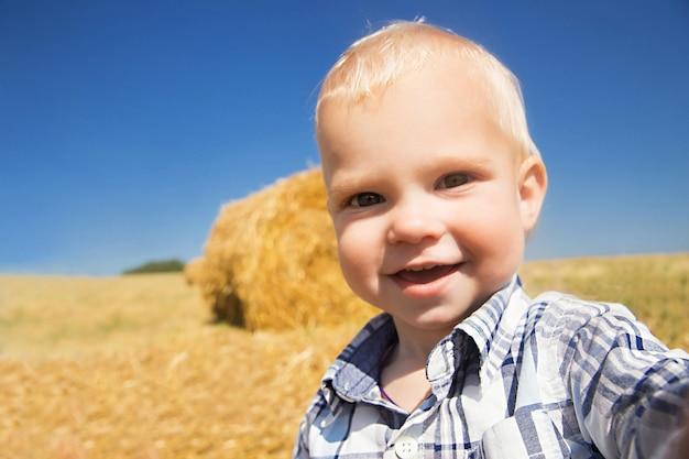 Heureux petit garçon à l'arrière-plan d'une botte de foin.