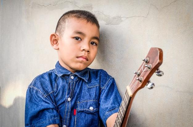 Heureux petit garçon asiatique portant une chemise en jeans jouent ukulélé
