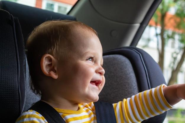 Heureux petit garçon assis dans le siège auto