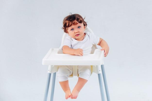 Heureux petit garçon assis sur fond de studio