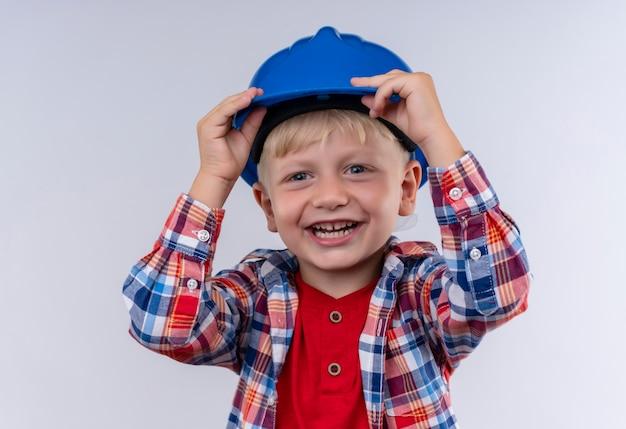 Un heureux petit garçon aux cheveux blonds portant chemise à carreaux tenant son casque bleu tout en regardant sur un mur blanc