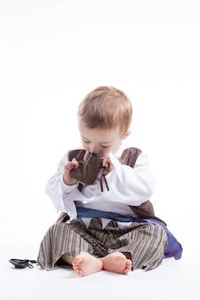 Heureux petit garçon caucasien, habillé comme un pirate jouant avec des pièces et des confettis. petit garçon et concept de costumes.