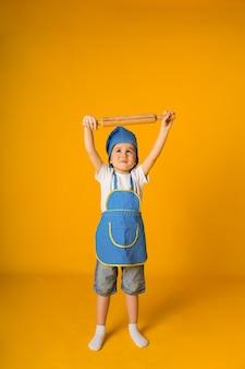 Heureux petit garçon en costume de chef tient un rouleau à pâtisserie en bois sur une surface jaune avec un espace pour le texte