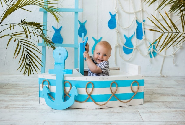 Heureux petit garçon dans une combinaison rayée se trouve dans un bateau en bois et tient le volant sur une digue