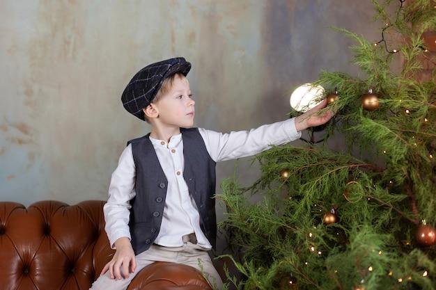Heureux petit garçon décore le sapin de noël