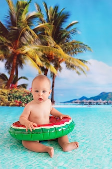 Heureux petit garçon enfant nage dans la mer dans une bouée de sauvetage en forme de pastèque