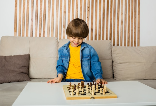 Heureux petit garçon est assis dans une pièce à jouer aux échecs