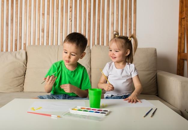 Heureux petit garçon et fille dessin avec des pinceaux et des peintures sur papier dans la chambre