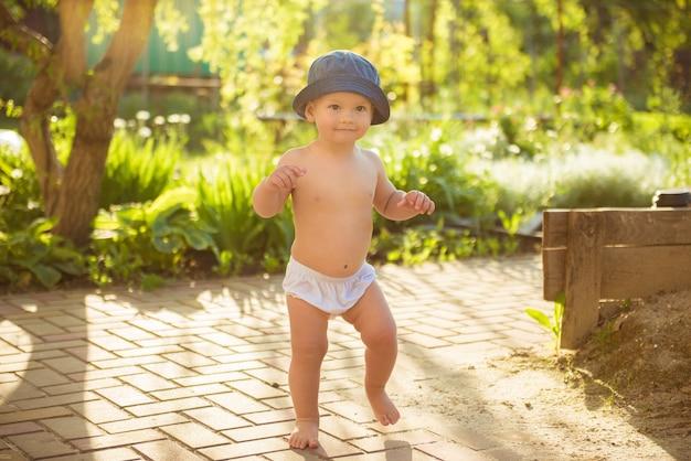 Heureux petit garçon jouant dans le parc dans un drôle de chapeau panama