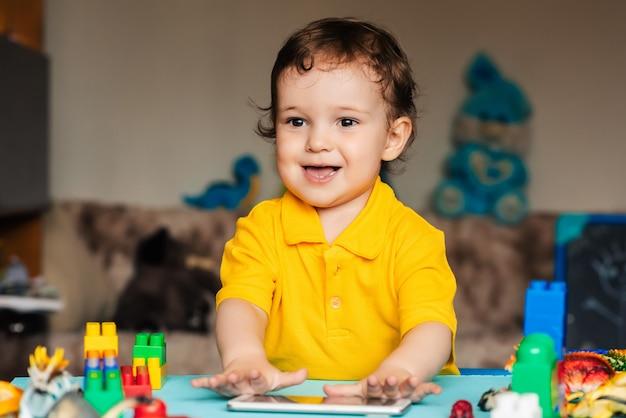 Heureux petit garçon jouant dans un smartphone à côté de jouets