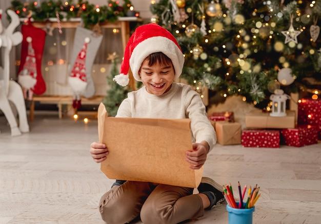 Heureux petit garçon avec lettre au père noël assis sur le sol dans une salle de fête avec arbre de noël