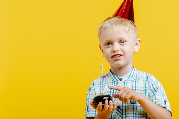 Heureux petit garçon mignon au chapeau d'anniversaire et avec un gâteau sur jaune.