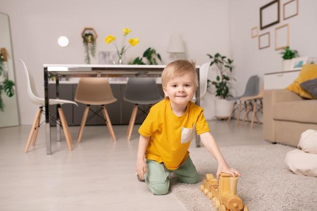 Heureux petit garçon mignon jouant avec un train en bois assis sur un tapis sur le sol sur fond de table et groupe de chaises autour