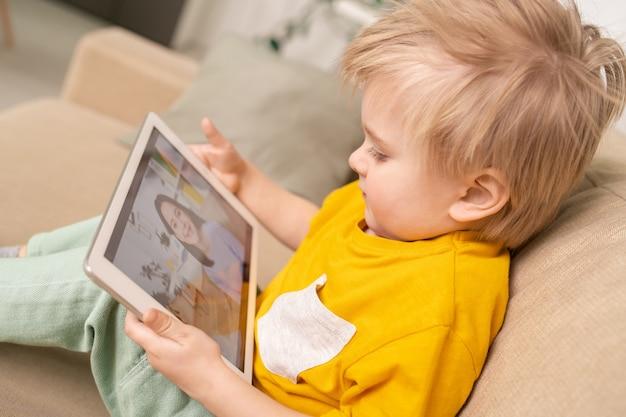 Heureux petit garçon mignon avec pavé tactile parlant à sa mère par vidéo-chat tout en vous relaxant sur le canapé dans l'environnement familial en quarantaine