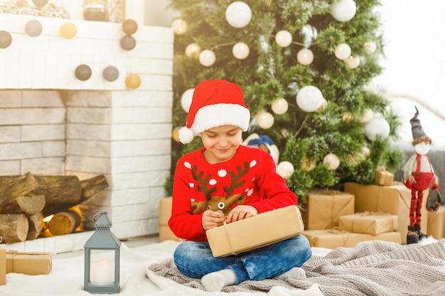 Heureux petit garçon ouvrant des cadeaux de noël près de l'arbre du nouvel an