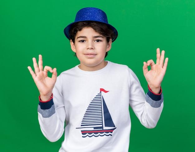 Heureux petit garçon portant un chapeau de fête bleu montrant la méditation isolée sur un mur vert