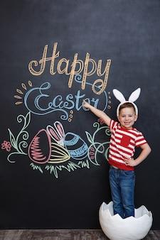 Heureux petit garçon portant des oreilles de lapin et debout à l'intérieur d'une grosse coquille d'oeuf fissurée