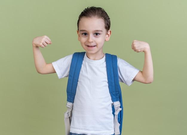 Heureux petit garçon portant un sac à dos regardant la caméra faisant un geste fort isolé sur un mur vert olive