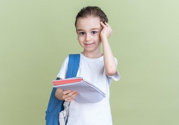 Heureux petit garçon portant un sac à dos tenant un bloc-notes touchant la tête regardant la caméra isolée sur un mur vert olive avec espace de copie