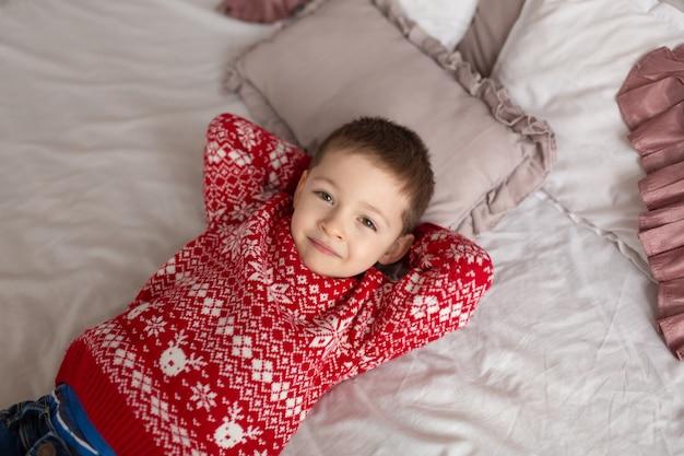 Heureux petit garçon en pull tricoté rouge, rêvez de cadeaux posés dans le lit