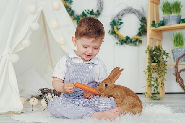 Heureux petit garçon riant jouant avec un bébé lapin