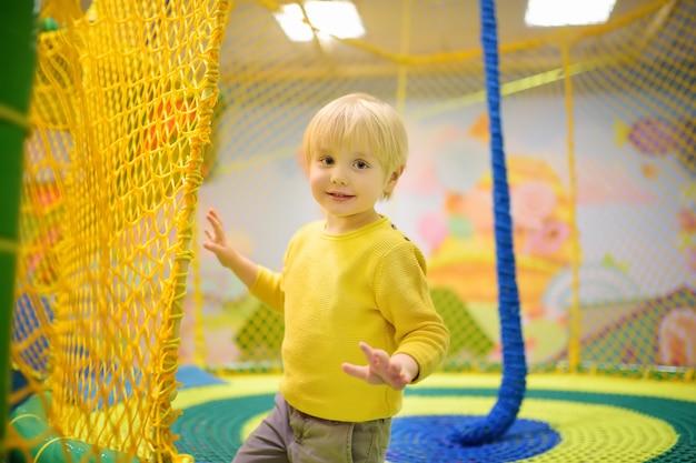 Heureux petit garçon s'amuser dans l'amusement dans le centre de jeu
