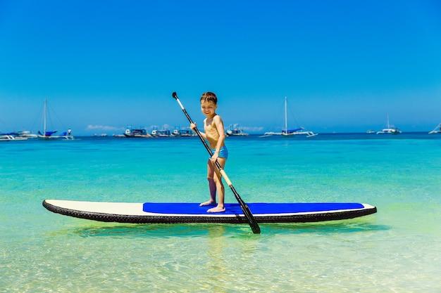Heureux petit garçon s'amuser sur une planche à pagaie dans la mer tropicale